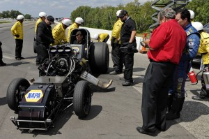 Funny Car driver Ron Capps (right, in blue) and team owner Don Schumacher look over the chassis of Capps' car after an engine explosion at Brainerd Int'l Raceway.